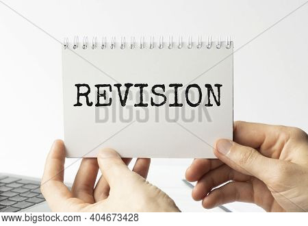 Revision, Text On White Paper In Hands