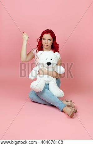 An Aggrieved, Humiliated Woman Holds A Large White Teddy Bear And Shakes Her Fist, Isolated On A Pin