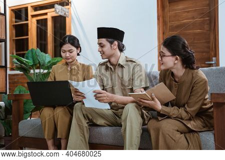 Three Civil Servants Working From Home Using Laptop Computers