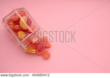Sweet Fruit Hard Candies Pouring Out Of The Glass Mason Jar On Colored Pink Background. Overhead Vie