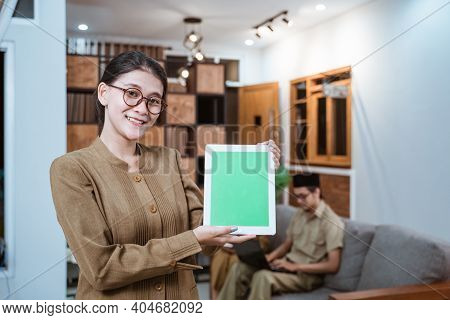 Female Teacher In A Civil Servant Uniform Wearing Glasses Smiling While Showing A Digital Tablet