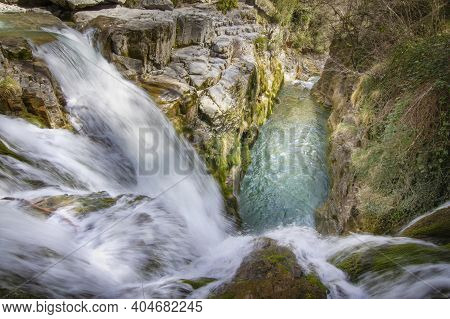 Waterfall Of A Mountain River Seen From Above, The Water Falls Into A Pool Of Crystalline Waters In