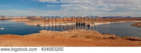 Lake Powell With A Receding Water Level Surrounded By Desert Landscape And Tower Butte In The Distan