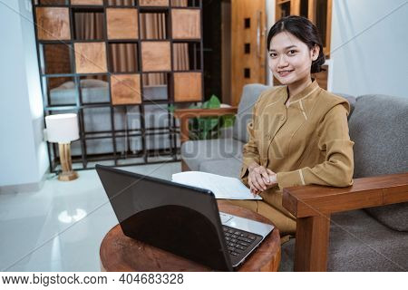 Woman In Government Servant Uniform Sitting On The Couch Using A Laptop Computer When Working From H