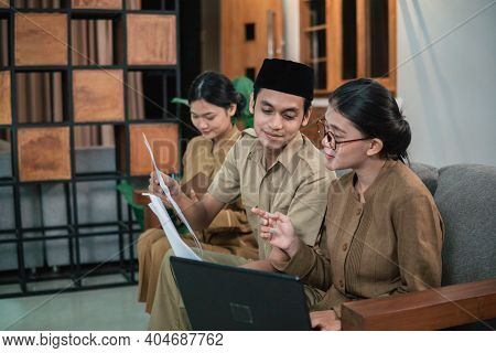 Man And Women Civil Servants Holding And Looking Paperwork When Sitting While Working Online
