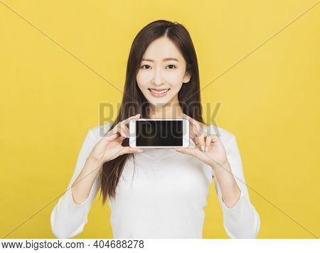 Smiling Casual Young Woman Holding Smartphone And Showing The Blank Screen