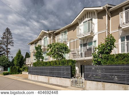 Residential Condo Building With Fenced Front Yard On Stormy Sky Background