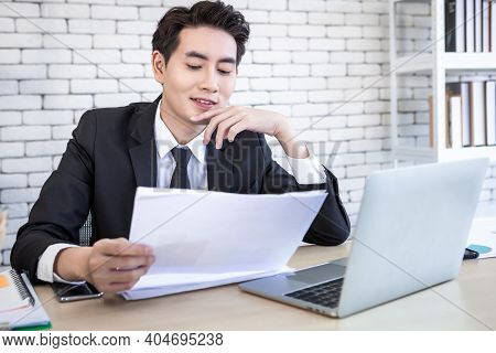 Asian Young Businessman Have Stressed See A The Document  Business Plan And Laptop Computer On Woode