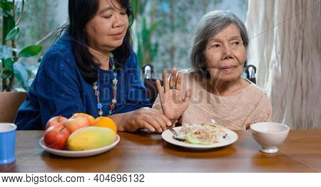 Senior Asian Woman Bored With Food At Home