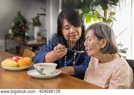 Daughter Is Feeding Elderly Mother With Soup.