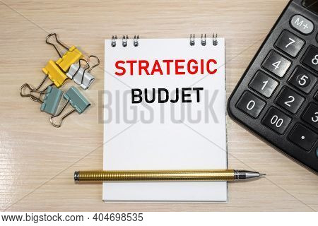 The Inscription Strategic Budget On A Notebook With A White Sheet. Black Calculator And Paper Clips.