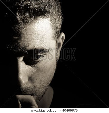 Thoughtful man on black background