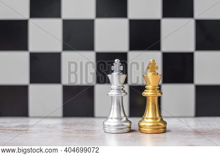 Gold And Silver Chess King Figure On Chessboard Against Opponent Or Enemy. Strategy, Conflict, Manag