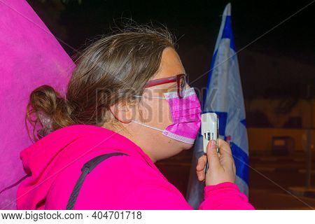 Haifa, Israel - January 23, 2021: Protestor With Flag And Megaphone Takes Part In The Black Flags Pr