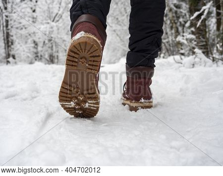 A Man In Boots Is Walking Through The Winter Forest. Bottom View Of Shoes, Selective Focus. Concept
