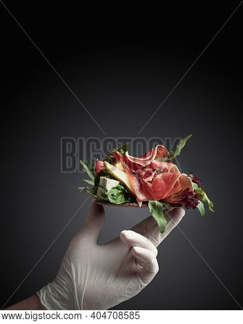Hand In Latex Glove With A Sandwich.  Sandwich With Prosciutto, Blue Cheese, And Greens.concept Imag