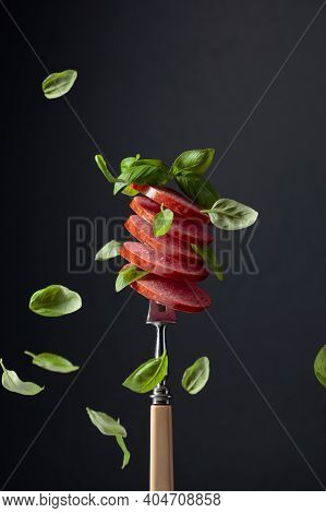 Sliced Smoked Sausage With Green Basil Leaves On A Fork.