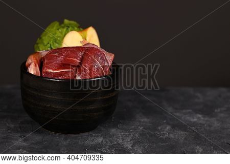 Bowl With Mixture Of Biologically Appropriate Raw Dog Food Containing Meat Chunks, Fish, Fruits And