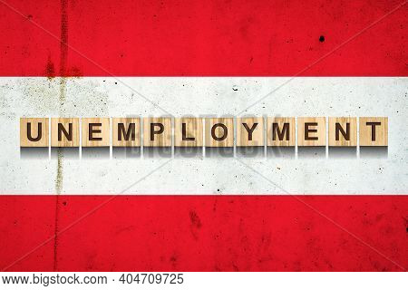 Unemployment. The Inscription On Wooden Blocks On The Background Of The Austria Flag. Unemployment G