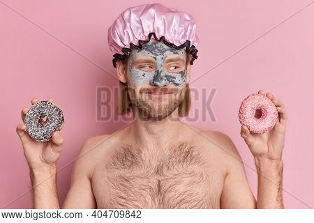 Horizontal Shot Of Happy Unshaven Man With Bob Hairstyle Holds Sweet Donuts Looks Gladfully Aside Ap