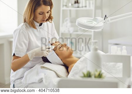 Female Beautician Makes A Procedure For Ultrasonic Skin Cleansing Of A Young Patient In A Beauty Spa