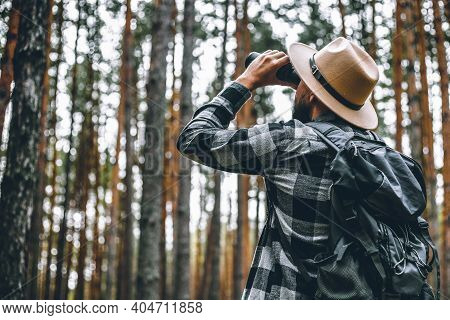 Male Tourist Looking Through Binoculars In The Forest