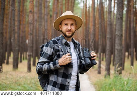 Young Man In A Hat With A Backpack And Binoculars In A Pine Forest. Hike In The Mountains Or Forest