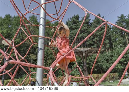 Active Young Child Girl Climbing The Spider Web Playground Activity. Children Summer Activities.