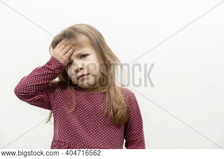 Children's Emotions. The Little Girl Has A Headache. The Child Holds On To The Forehead. Mock Up Wit