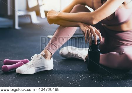 Sport Woman Workout At Fitness Center With Relax And Taking A Break Beautiful Girl Holding Protein S