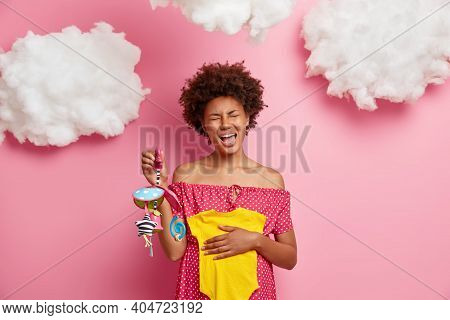 Unhappy Dark Skinned Woman With Afro Hair Awaits For Baby Holds Mobile Toy Bodysuit Over Big Tummy W