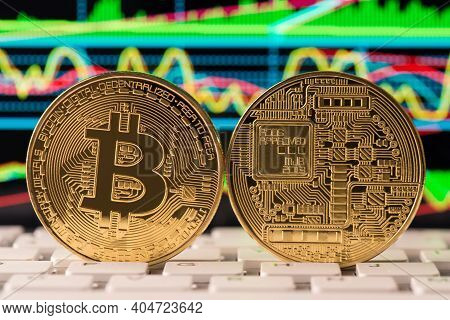 Close Up Photo Of Golden Bitcoin Showing Front And Back Sides On Background With Bright Graph Standi