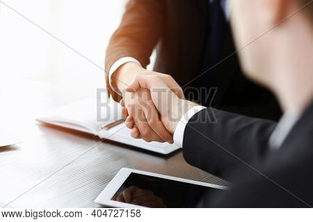 Businessman Shaking Hands With His Colleague Above The Glass Desk In Sunny Modern Office, Close-up.