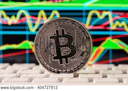 Closeup Photo Image Of Shiny Silver Bitcoin Standing On Keyboard Buttons With Multicolored Diagrams