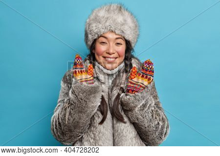 Pretty Eskimo Woman Dresses For Cold Weather Smiles Happily Wears Fur Coat And Hat Raises Hands In M