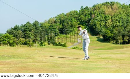 Golfer Asian Man Swing And Hitting Golf Ball Practice At Golf Driving Range And Fairway With Bag Gol