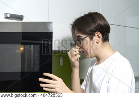A Man Smells An Unpleasant Smell From The Microwave In The Kitchen.