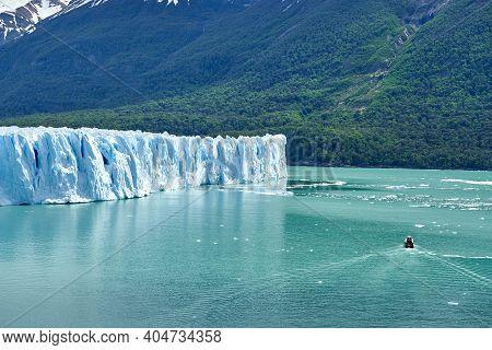 Blue Ice Of Perito Moreno Glacier In Glaciers National Park In Patagonia, Argentina With A Tourist B