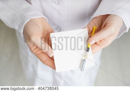 Doctor Holds A Vaccine Syringe And Empty White Mockup Paper