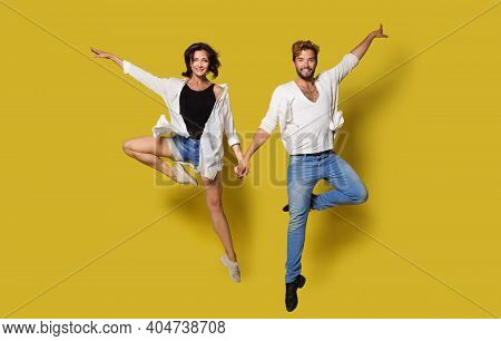 Jumping Couple, Full Length Joyful People Holding Hands, Isolated Yellow Background
