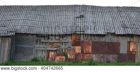 Old Aged Weathered Wooden Shack, Grey Plated Wood Boarding Hut Wall, Patched Planks, Rusted Metal Pl