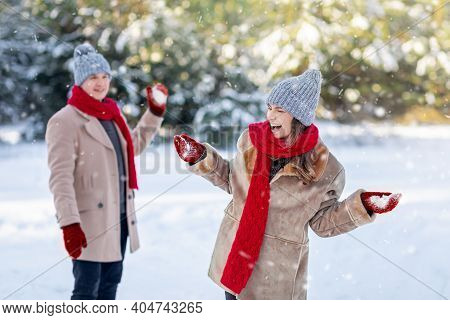 Emotional Man And Woman Playing Snowballs At City Park, Copy Space. Happy Young Couple In Stylish Wa