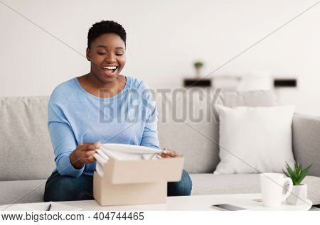 Delivery Concept. Smiling Chubby Black Woman Unboxing Cardboard Package, Sitting On The Couch In Liv