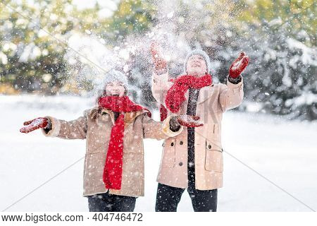 Cheerful Young Man And Woman Enjoying Snow On Cold Winter Day Over Beautiful White Forest Or City Pa