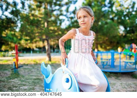 A Lovely Beautiful Little Girl In A Wonderful Pink Delicate Long Dress Sits On A Small Swing, A Warm