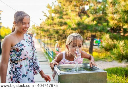 Two Funny Cheerful Wonderful Sisters Drink Cool Fresh Water From A Small Fountain In A Summer Warm S