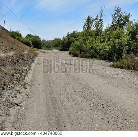 Dry Stony Dusty Ground With Grass And Bushes Near Small Hill. Rustic Road Texture Background.