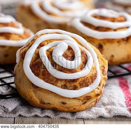 Closeup Of Baked Cinnamon Rolls With White Icing On A Cooling Rack