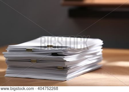 Stack Of Blank Paper With Binder Clips On Wooden Table Indoors