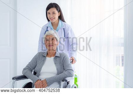 Happy Senior Woman Sitting On Wheelchair, A Young Nurse Takes Care Of A Disabled Elderly Woman, Seni